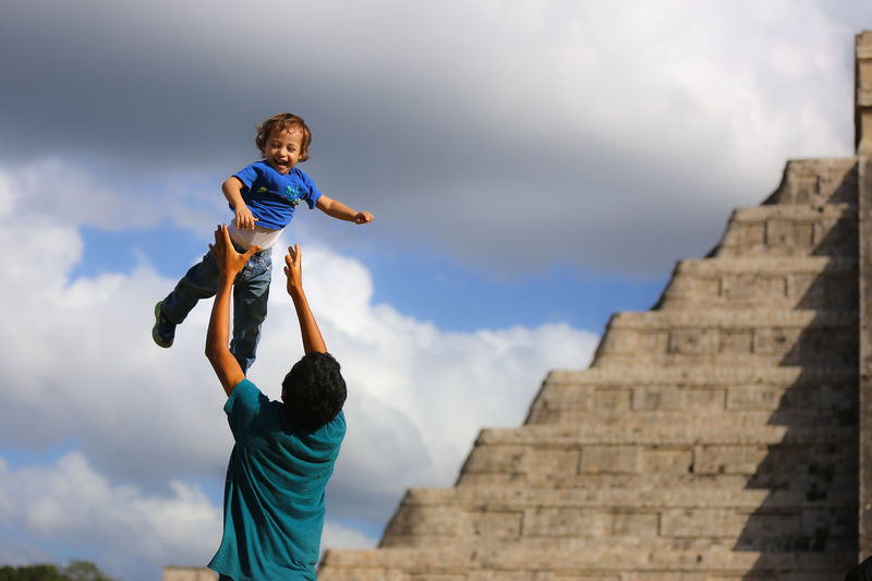 Rear View Of Man Tossing Cheerful Son Against Kukulkan Pyramid