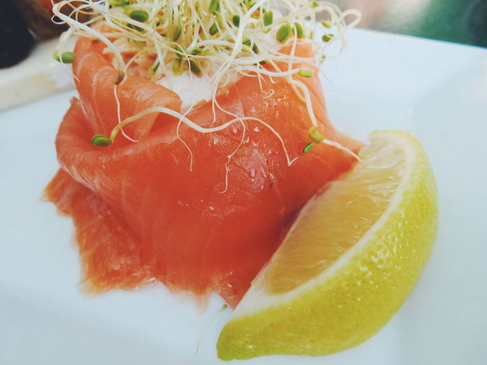 Close-up of smoked salmon by lemon in plate