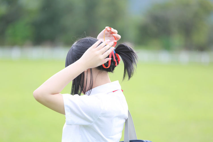 Young Woman Standing In Park While Tying Pony Tail
