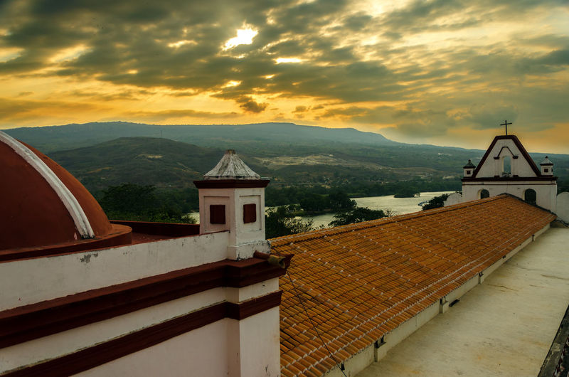 Historic Church And Mountains Against Cloudy Sky During Sunset