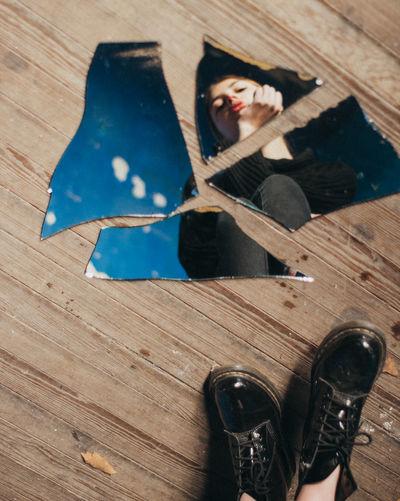 Reflection of woman in broken mirror on hardwood floor
