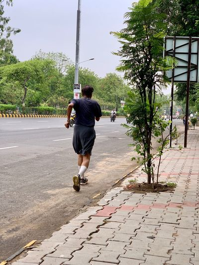 Runner Full Length Real People Rear View One Person Plant Lifestyles Tree Footpath Casual Clothing Men Day Leisure Activity Street Nature Outdoors City Motion Walking The Way Forward
