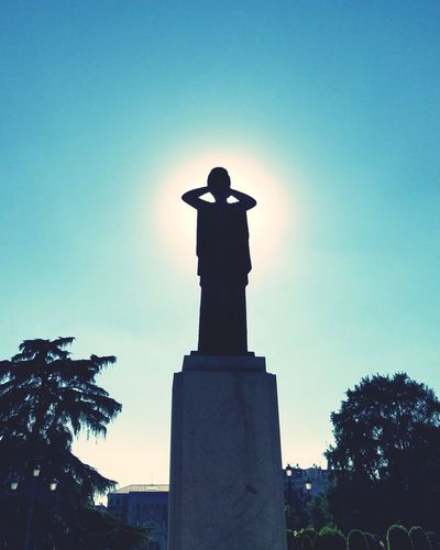 Low angle view of silhouette statue against sky