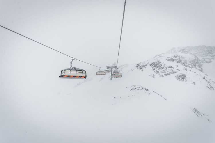 Snow Winter Cold Temperature Cable Car Mountain Overhead Cable Car Transportation Ski Lift Mode Of Transportation Cable Beauty In Nature White Color Scenics - Nature Nature Covering Day Travel Environment Snowcapped Mountain No People Mountain Range Outdoors Electricity  Extreme Weather
