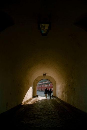 People walking on footpath in tunnel