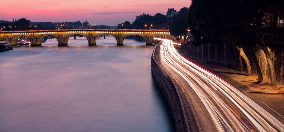 High Angle View Of Light Trails On Road By River During Sunset In City