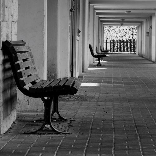 Empty bench in corridor of building