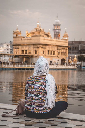 Rear view of woman sitting by lake and golden temple against sky
