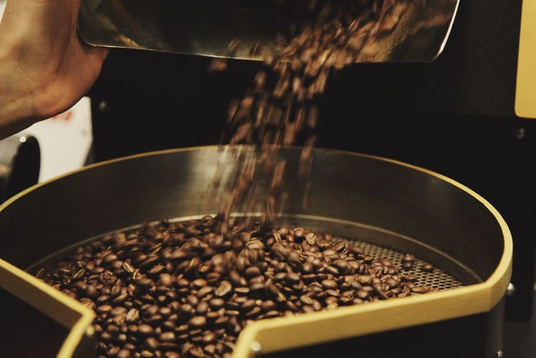 Cropped hand of worker pouring roasted coffee beans on strainer