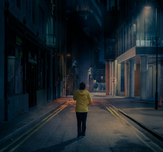 Rear view of woman walking on street amidst buildings at night
