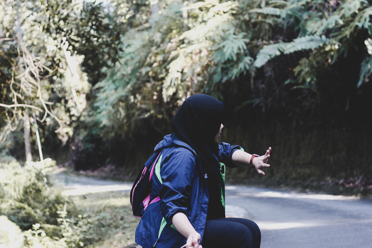 Side view of woman wearing hijab sitting by road in forest