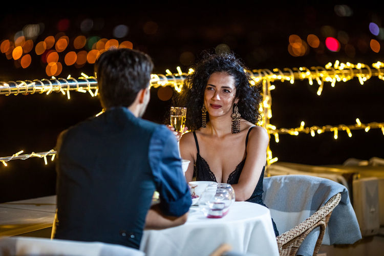 Young Couple Having Drinks At Table On Terrace