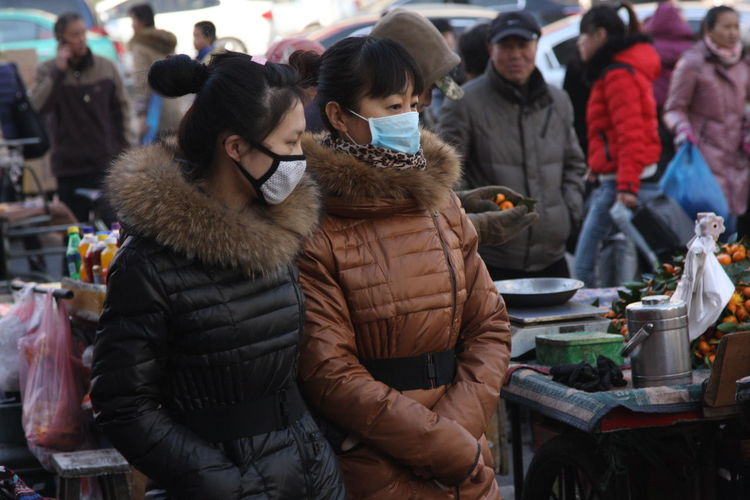 Female friends wearing mask while standing in market