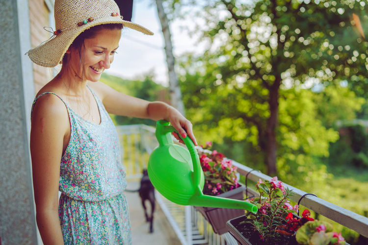Woman watering plants with can while standing in balcony