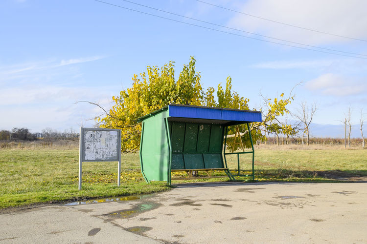 Bus Stop On Field Against Sky