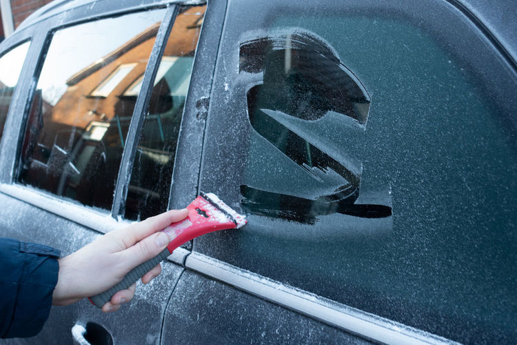 Close-up of hand cleaning car window of snow and ice in winter for safe driving