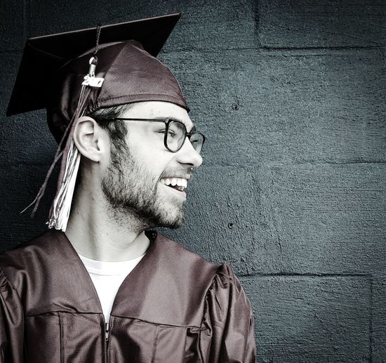 Smiling Young Man Wearing Graduation Gown Against Wall