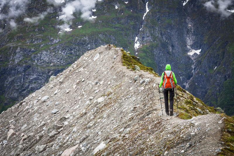 Full length rear view of woman hiking on mountain peak