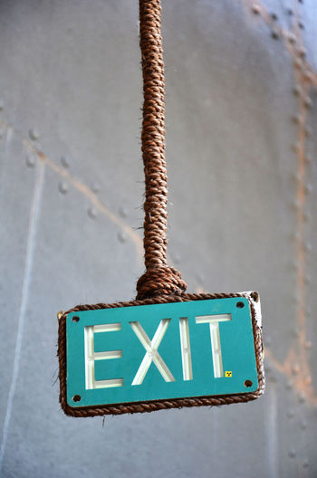 Close-up of exit sign against the wall