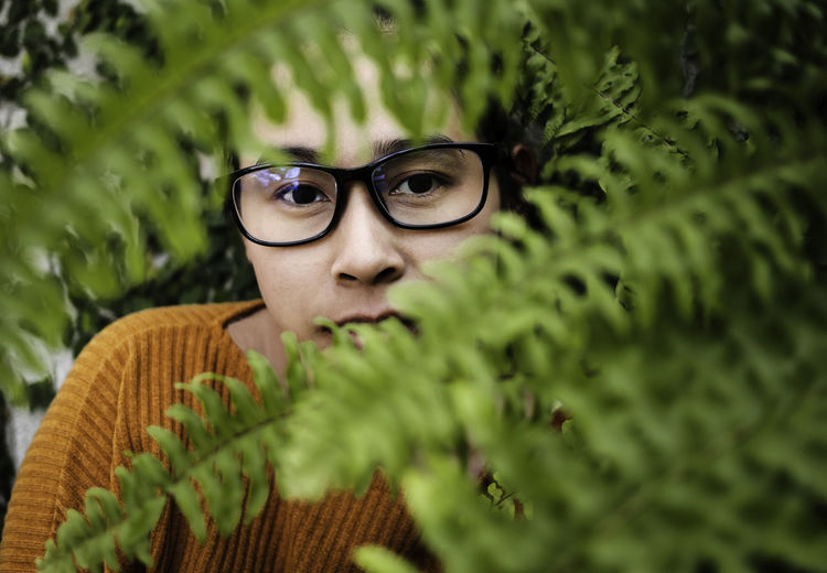Close-up portrait of young woman wearing eyeglasses seen through leaves