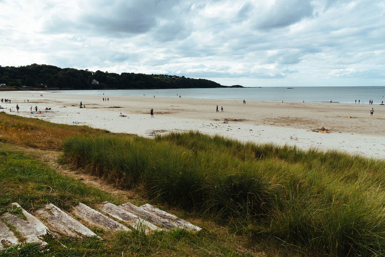 Scenic view of beach in Brittany a cloudy day of summer Nature Day Outdoors Brittany France Water Beach Land Sky Sea Grass Cloud - Sky Plant Beauty In Nature Scenics - Nature Tranquility Tranquil Scene Horizon Horizon Over Water Marram Grass Tranquility Summer Sand Incidental People