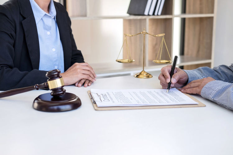 Cropped Image Of Man Signing On Paper With Lawyer In Courtroom