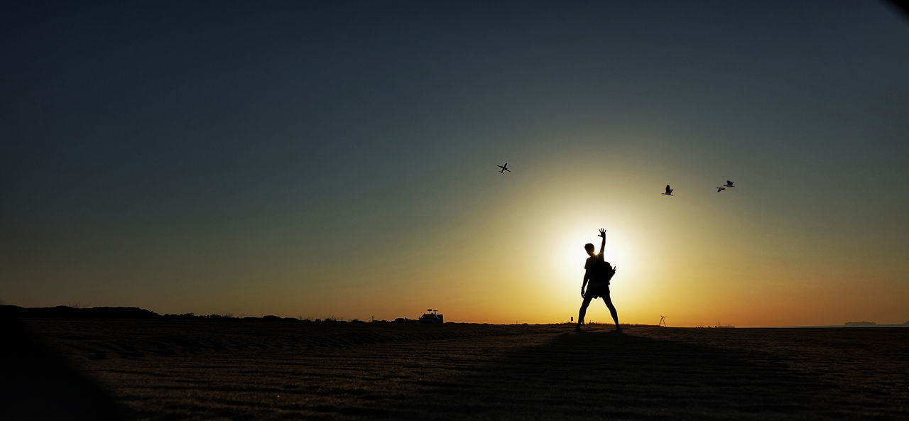 sunset, sky, flying, silhouette, scenics - nature, beauty in nature, real people, land, nature, vertebrate, leisure activity, lifestyles, orange color, bird, copy space, people, tranquility, standing, sun, outdoors