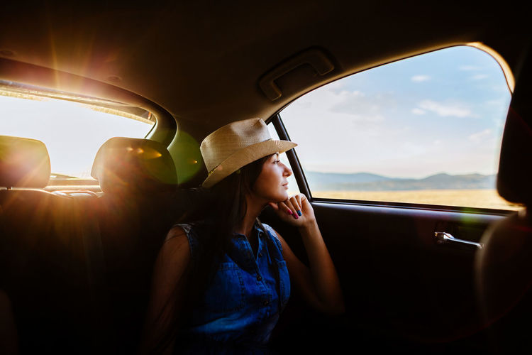 woman travel and dreaming by car with sunlight and picturesque view. Travelling by car. Adult Adventure Car Car Interior Driving EyeEm Best Edits EyeEmBestPics Hat Journey One Person One Woman Only One Young Woman Only Only Women People Rural Scene Sitting Sky Sunlight Transportation Travel Vacations Vehicle Interior Women Young Adult Young Women