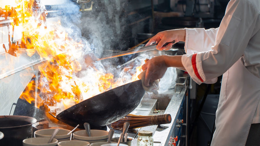 Chef stir fry cooking in kitchen, professional chef fire cooking of restaurant