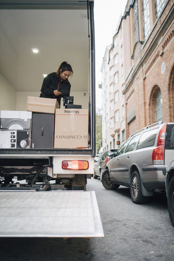 Woman standing on car in city