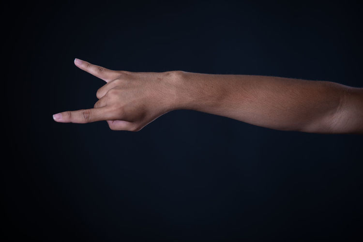 Close-up of man hand over black background