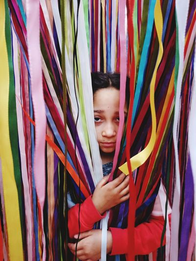 Portrait of girl holding multi colored ribbons