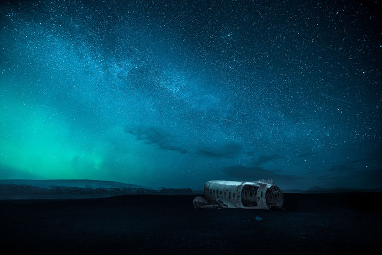 Artistic image of the famous DC-3 plane wreck with stars of milky way and northern lights in Iceland. Plane Darkness Aircraft Wreck Crash Site Aurora Borealis DC-3 Plane Wreck Travel Destinations Landscape Nordic Countries Iceland Night Northern Lights Astronomy Astrology Sign Space Galaxy Milky Way Star - Space Constellation Science Sky Space And Astronomy Aurora Polaris Star Field Starry Visual Creativity