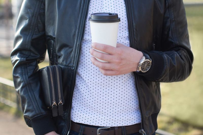 Midsection of man holding disposable cup