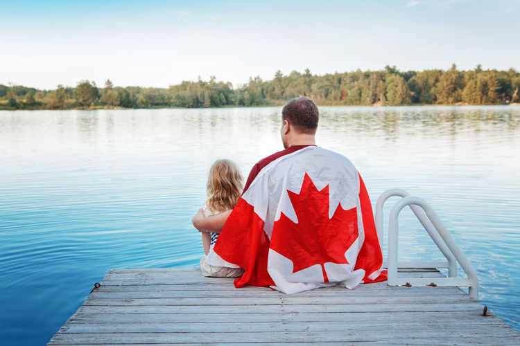 Father and daughter wrapped in large canadian flag sitting on wooden pier by lake. canada day