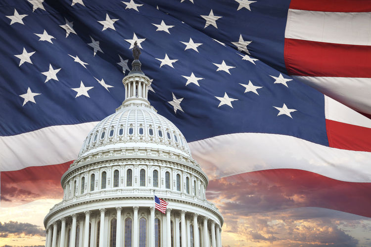 United States Capitol building with an American flag and dramatic sky behind American Flag Capitol Dramatic Sky Red United States Waving America Architecture Blue Building Exterior Clouds Democracy Government Montage National Icon No People Patriotism Photography Star Striped White