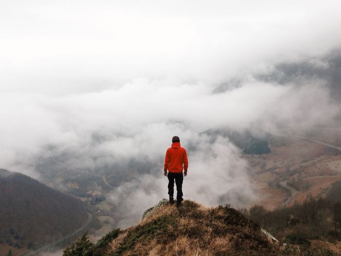 Rear view of man standing on mountain peak during foggy weather