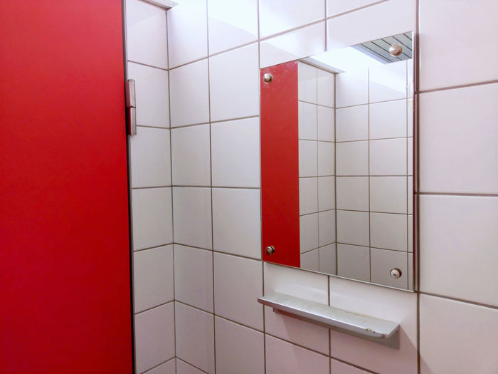 mirror in changing room at indoor swimming pool /from series: one room Changing Room Minimalism Red And White Architecture Changing Room Locker Room Mirror Red Swimming Architectural Detail Forms And Colors Forms And Shapes Geometric Shape Hygiene Indoors  Interior Interior Design Mirror Privacy Private Red Red Color Reflection Simplicity Swimming Pool Tile White White Color