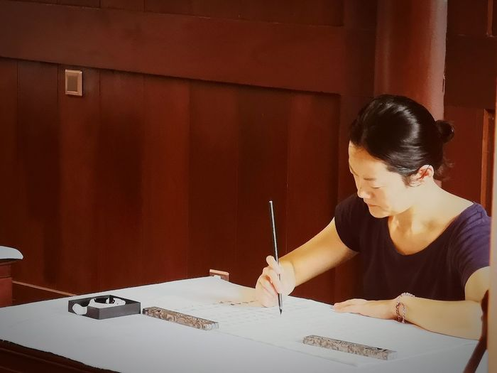 Woman working at desk against wall