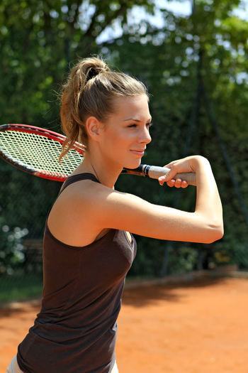 Young woman playing tennis, female tennis player Court Fun Happiness Happy Holidays Power Tennis Tennis Player Woman Action Active Activity Competition Female Game Girl Leisure Activity One Person Outdoors Pretty Sport Sportive Summer Tennis Racket Young Adult