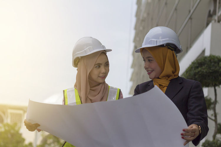 Happy female architects looking at each other while holding blueprint against clear sky