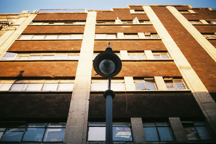 Low angle view of street light against building