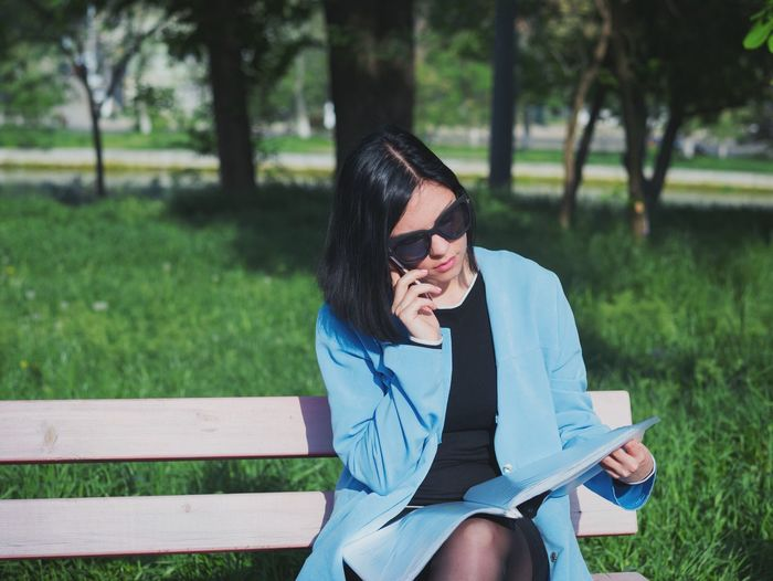 Woman reading document while sitting on bench at park
