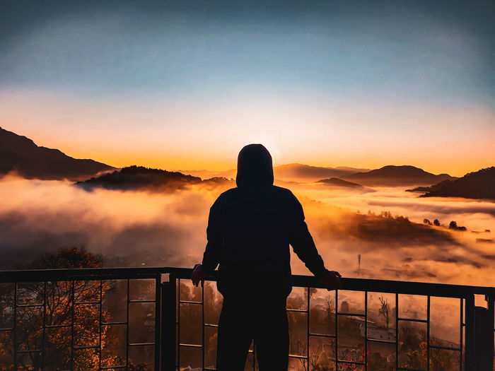 City above of the clouds and a wonderful sunrise surrounded by fog and muntains.and man against  sun
