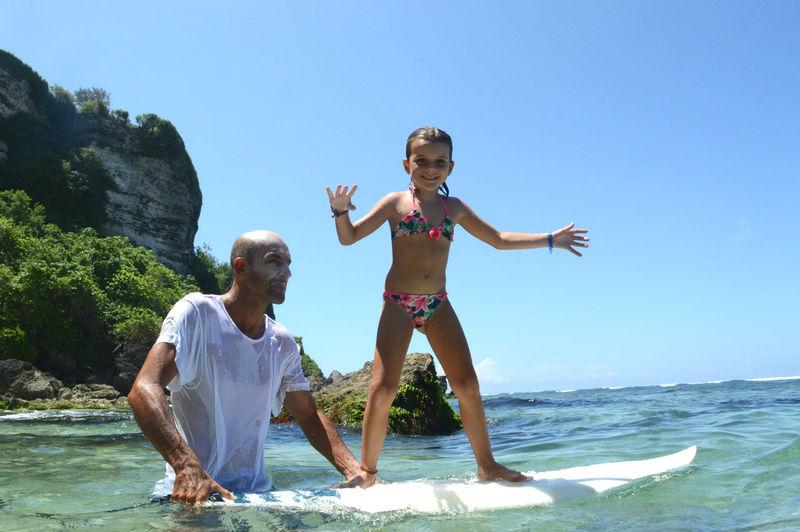 Man teaching girl to surf in sea