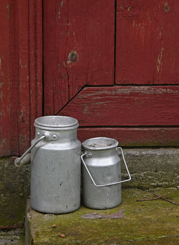 Fresh village milk delivery - two vintage metal milk can containers at door steps Can Cans Close-up Container Containers Delivery Diary Door Doortodoor Fresh Metal Milk Milk Can Morning Old Porch Red Rustic Staircase Steps Vessels Village Vintage Two Is Better Than One Lieblingsteil