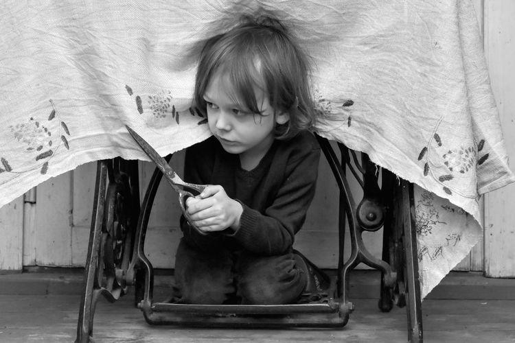 Child Children Only Childhood One Person Elementary Age Indoors  Real People Boy Under The Table Scissors Leisure Activity Cutting Naughty♥ Naughtyboy Tablecloth Lithuania Blackandwhite Black And White