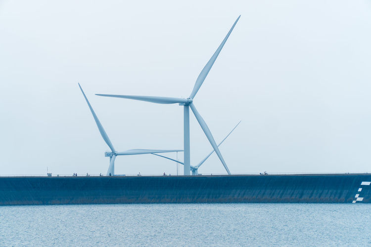 Windmills on landscape against clear sky