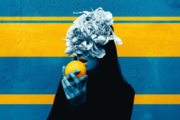 Woman wearing flowers on hair holding orange fruit against wall