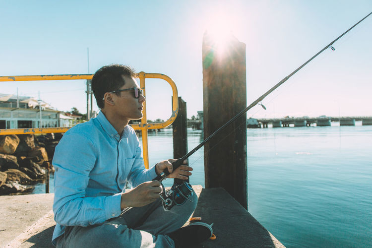 Young man fishing while sitting on jetty against clear sky